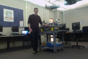 Senior Jason Merlo poses with the robot test chassis. Photo by Simon Sun.