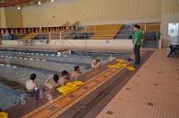 Varsity swim coach meeting with team mid practice
